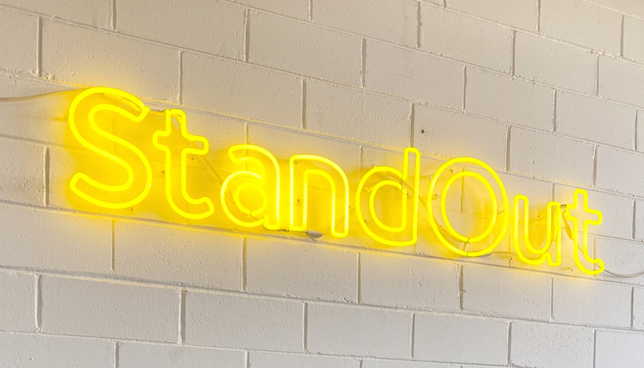 Image of neon 'stand out' sign from WR office